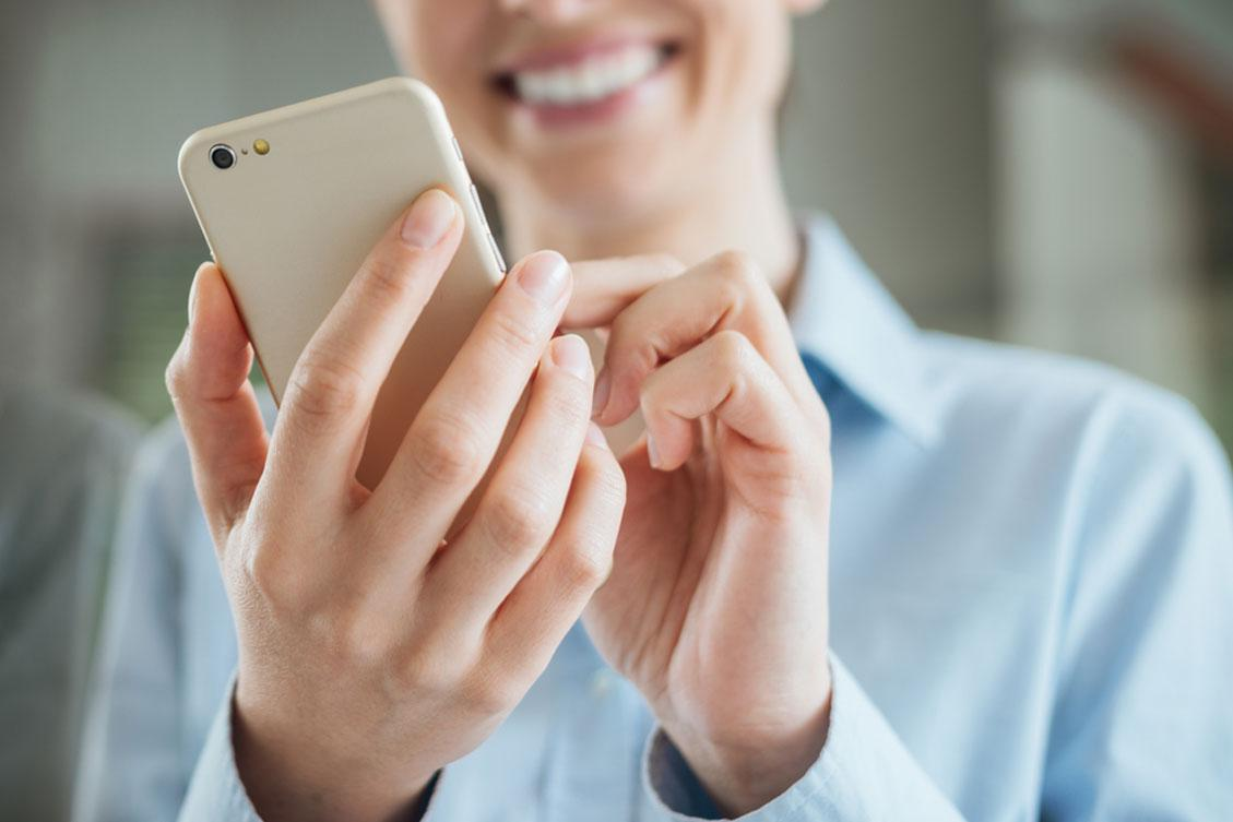 A top SEO reviews analytics data on her mobile device in Harrington